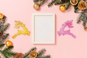 Minimal creative flat lay of winter christmas traditional composition and new year holiday season. Top view mockup black picture frames for text on pink background. Mock up and copy space photography. photo