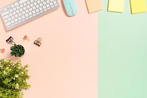Minimal work space - Creative flat lay photo of workspace desk. Top view office desk with keyboard, mouse and adhesive note on pastel green pink color background. Top view with copy space photography.