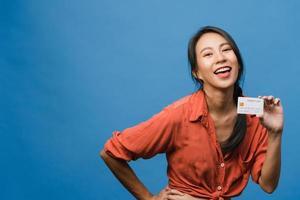 Joven mujer asiática muestra una tarjeta bancaria de crédito con expresión positiva, sonríe ampliamente, vestida con ropa informal sintiendo felicidad y parada aislada sobre fondo azul. concepto de expresión facial. foto