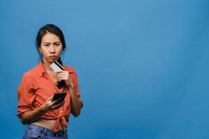 Young Asia lady using phone and credit bank card with negative expression, excited screaming, cry emotional angry in casual cloth and stand isolated on blue background. Facial expression concept. photo