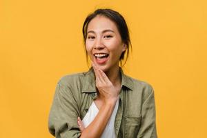 Jovencita asiática con expresión positiva, sonrisa amplia, vestida con ropa casual y mirando a cámara sobre fondo amarillo. feliz adorable mujer alegre se regocija con el éxito. concepto de expresión facial. foto