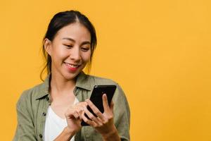 Jovencita asiática que usa el teléfono con expresión positiva, sonríe ampliamente, vestida con ropa casual sintiendo felicidad y parada aislada sobre fondo amarillo. feliz adorable mujer alegre se regocija con el éxito. foto