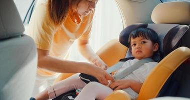 Happy cheerful Asia family mom fastening seat belt of child car seat before go for ride with toddler girl preparing for trip in car. Safety driving concept. photo