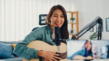 Teenage Asia girl influencer play guitar music use microphone record with smartphone for online audience listen at home. Female podcaster make audio podcast from her home studio, Stay at home concept. photo