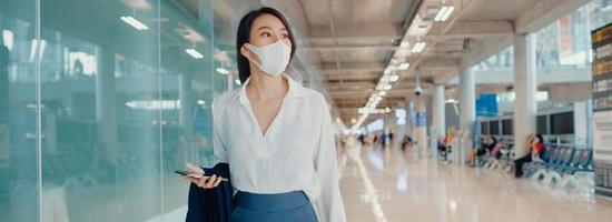Chica de negocios asiática usa un teléfono inteligente para registrar la tarjeta de embarque, camine con el equipaje hasta la terminal del vuelo nacional en el aeropuerto. pandemia de covid de viajeros de negocios, fondo de banner panorámico con espacio de copia. foto