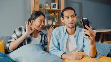 Feliz joven pareja asiática hombre y mujer se sientan en el sofá usando la videollamada facetime del teléfono inteligente con amigos y familiares en la sala de estar en casa. quedarse en casa cuarentena, distanciamiento social, concepto de joven casado. foto