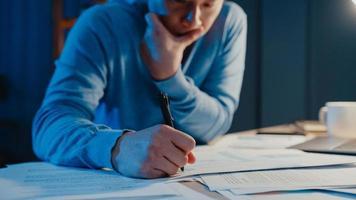 Hombre de negocios autónomo asiático se enfoca en el tipo de trabajo en la computadora portátil ocupado con un gráfico lleno de papeleo en el escritorio en la sala de estar en casa horas extras por la noche, trabaja desde casa durante el concepto de pandemia covid-19. foto