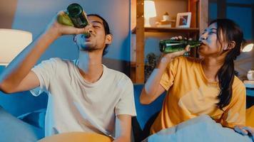 Feliz pareja asiática joven mirando a la cámara disfrutar de un evento de fiesta nocturna en línea sentarse en el sofá videollamada con amigos tostar beber cerveza a través de una videollamada en línea en la sala de estar en casa, concepto de distanciamiento social. foto