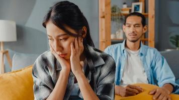 Upset asian couple wife sit on couch listen to furious husband yelling feel unhappy talk negative to her. Couple have fight or disagreement at home, Couple problem, family married toxic relationship. photo