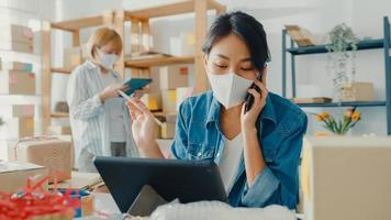 Young Asia businesswomen wear face mask using mobile phone call receiving purchase order and check product on stock work at home office. Small business owner, online market delivery freelance concept. photo