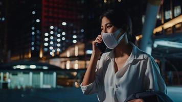 Serious dissatisfied upset young Asia businesswoman wear medical face mask talk via phone while walk alone outdoor in urban city night. Business on go, Social distancing to prevent spread of COVID-19. photo