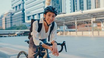 La empresaria asiática ir a trabajar en el stand de la oficina y sonriente llevar mochila mirar a la cámara con bicicleta en la calle alrededor de la construcción de una ciudad. viaje en bicicleta, viaje en bicicleta, concepto de viajero de negocios. foto