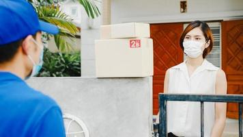 Young postal delivery courier man wear face mask handling parcel box for send to customer at house and Asian female receive delivered package outdoors. Lifestyle new normal after corona virus concept. photo