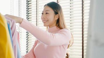 Bella y atractiva joven asiática eligiendo su ropa de traje de moda en el armario de la casa o tienda. chica piensa qué ponerse camisa casual. Vestuario de casa o tienda de ropa, vestuario. foto