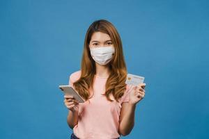 joven asiática con mascarilla médica usando teléfono y tarjeta bancaria de crédito con expresión positiva, sonríe ampliamente, vestida con ropa casual y de pie aislado sobre fondo azul. foto