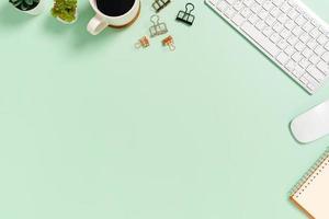 espacio de trabajo mínimo: foto creativa plana del escritorio del espacio de trabajo. Escritorio de oficina de vista superior con teclado y mouse sobre fondo de color verde pastel. vista superior con espacio de copia, fotografía plana.