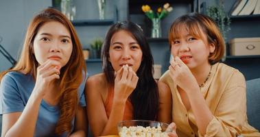 Attractive Asian lovely lady girl group positive glad cheerful with casual have fun and enjoy watch online movie entertainment on couch in living room at home. Lifestyle activity quarantine concept. photo