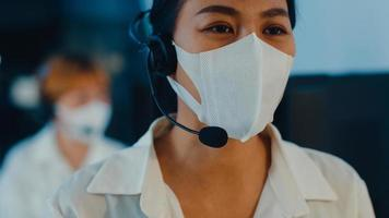 Millennial Asia young call center team or customer support service executive wearing face mask prevent covid-19 using computer and microphone headset working technical support in late night office. photo