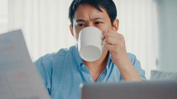 Freelance Asia guy casual wear using laptop and drink coffee in living room at house. Working from home, remotely work, distance education, social distancing, quarantine for corona virus prevention. photo