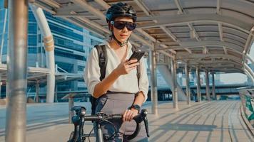 feliz empresaria asiática con mochila utiliza teléfonos inteligentes en la ciudad de pie en la calle con bicicleta ir a trabajar en la oficina. chica deportiva usa su teléfono para trabajar. viaje diario al trabajo, viajero de negocios en la ciudad. foto