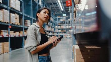 Gerente atractiva joven empresaria de Asia en busca de productos mediante tableta digital que controla los niveles de inventario de pie en el centro comercial minorista. distribución, logística, paquetes listos para embarque. foto