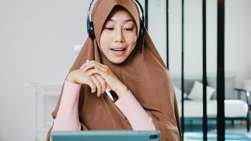 Asia muslim lady wear headphone using digital tablet talk to colleagues about sale report in conference video call while working from home at kitchen. Social distancing, quarantine for corona virus. photo