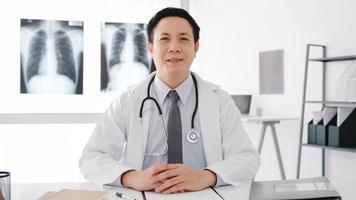 Confiado joven médico de Asia en uniforme médico blanco con estetoscopio mirando a cámara y sonriendo durante la llamada de videoconferencia con el paciente en el hospital de salud. concepto de consulta y terapia. foto