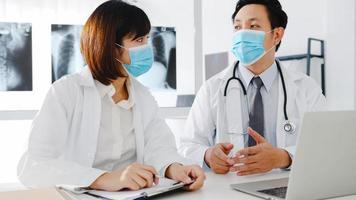 Equipo médico de asia hombres y mujeres jóvenes graves con máscaras protectoras discutiendo el resultado de la tomografía computarizada en el consultorio del hospital. distancia social, estilo de vida nuevo normal después del virus corona. foto