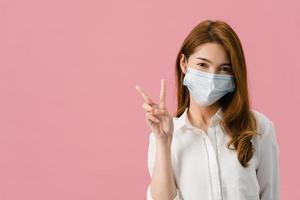 Young Asia girl wearing medical face mask showing peace sign, encourage with dressed in casual cloth and looking at camera isolated on pink background. Social distancing, quarantine for corona virus. photo