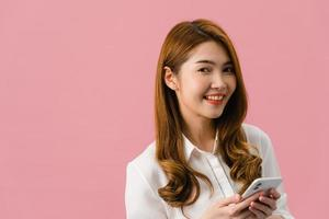 Surprised young Asia lady using mobile phone with positive expression, smiles broadly, dressed in casual clothing and looking at camera on pink background. Happy adorable glad woman rejoices success. photo