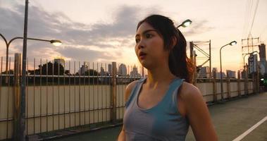Hermosa joven atleta asiática se ejercita porque se siente cansada después de correr en un entorno urbano. Jovencita japonesa ejercitarse vistiendo ropa deportiva en el puente de la pasarela temprano en la mañana. foto
