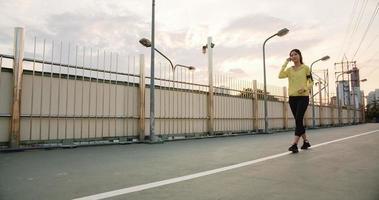 hermosa joven atleta de asia ejercicios de dama con teléfono inteligente para escuchar música mientras se ejecuta en un entorno urbano. Adolescente coreana vistiendo ropa deportiva en el puente de la pasarela temprano en la mañana. foto