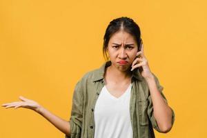 jovencita asiática habla por teléfono con expresión negativa, gritos emocionados, gritos emocionales enojados en ropa casual y se para aislado sobre fondo amarillo con espacio de copia en blanco. concepto de expresión facial. foto