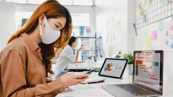 Asia businesswoman entrepreneur wearing face mask for social distancing in new normal situation for virus prevention while using laptop and phone back at work in office. Lifestyle after corona virus. photo