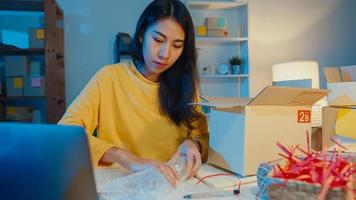 Young Asia businesswoman packing glass use bubble wrap for packing support damage fragile product in home office at night. Small business owner, online market delivery, lifestyle freelance concept. photo
