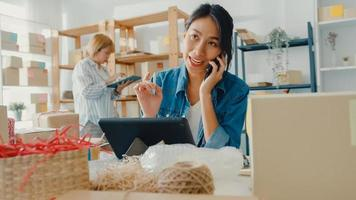 Young Asia businesswomen using mobile phone call receiving purchase order and check product on stock work at home office. Small business owner, online market delivery, lifestyle freelance concept. photo