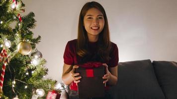 Mujer joven de Asia mediante videollamada de teléfono móvil hablando con pareja con caja de regalo de Navidad, árbol de Navidad decorado con adornos en la sala de estar en casa. festival navideño de navidad y año nuevo foto