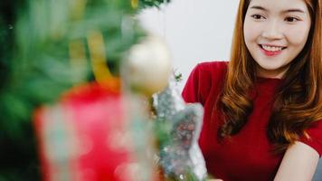 Asian female decorated with ornament on Christmas tree at Christmas and New Year festival in living room at home. Xmas celebration event preparation or winter holidays festival indoor party concept. photo