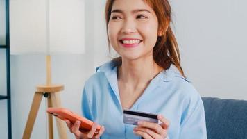 Jovencita asiática usa teléfonos inteligentes, compra con tarjeta de crédito y compra Internet de comercio electrónico en la sala de estar de la casa. quedarse en casa, compras en línea, autoaislamiento, distancia social, cuarentena por coronavirus. foto
