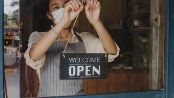 Joven asiática usa una mascarilla que gira un letrero de cerrado a abierto en la puerta mirando hacia afuera esperando a los clientes después del cierre. propietario de pequeñas empresas, alimentos y bebidas, concepto de reapertura de negocios. foto