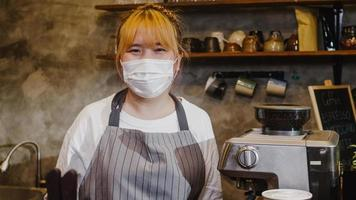 Portrait young Asia girl waitress wear medical face mask feeling happy smile waiting for clients after lockdown at urban cafe. Owner small business, food and drink, business reopen again concept. photo