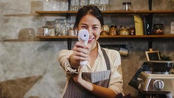 Retrato del personal femenino del restaurante asiático joven que usa el verificador del termómetro infrarrojo o la pistola de temperatura en la frente del cliente antes de ingresar al café restaurante urbano. estilo de vida nuevo normal después del virus corona. foto