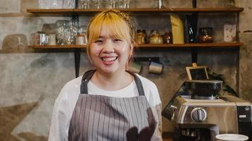 Portrait young Asian woman barista feeling happy smiling at urban cafe. Small business owner Korean girl in apron relax toothy smile looking to camera standing at the counter in coffee shop. photo