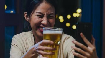 joven asiática bebiendo cerveza divirtiéndose feliz momento fiesta nocturna evento de año nuevo celebración en línea a través de videollamada por teléfono en casa por la noche. distanciamiento social, cuarentena para la prevención del coronavirus. foto