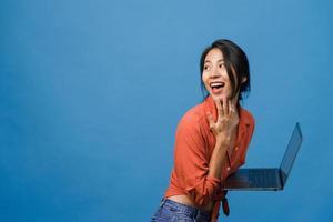 Jovencita asiática usando laptop con expresión positiva, sonríe ampliamente, vestida con ropa casual sintiendo felicidad y parada aislada sobre fondo azul. feliz adorable mujer alegre se regocija con el éxito. foto
