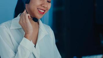 Millennial Asia young call center agent or customer support service executive using computer and microphone headset working technical support in late night office. Telemarketing or sales job concept. photo