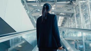 chica de negocios asiática usa mascarilla arrastre soporte de equipaje en la escalera mecánica mire alrededor camine hasta la terminal en el aeropuerto internacional. pandemia de covid viajero de negocios, concepto de distanciamiento social de viajes de negocios. foto