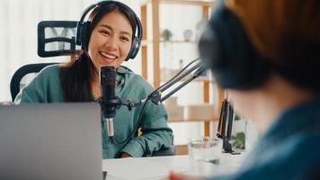 asia girl radio locutor grabar podcast usar micrófono usar auriculares entrevista celebridad invitado contenido conversación hablar y escuchar en su habitación. podcast de audio desde casa, concepto de equipo de sonido. foto