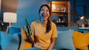 Feliz joven asiática mirando a la cámara disfrutar de un evento de fiesta nocturna en línea con amigos brindis beber cerveza a través de videollamadas en línea en la sala de estar en casa, quedarse en casa cuarentena, concepto de distanciamiento social. foto