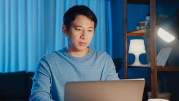 Asia empresario independiente se concentra en trabajar escribiendo en una computadora portátil en línea de forma remota desde la empresa en el escritorio en la sala de estar en casa horas extras por la noche, trabajar desde casa durante el concepto de pandemia covid-19. foto